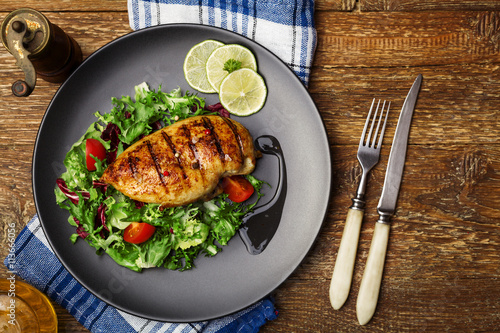 plakat Grilled chicken breast with green salad on a black plate.