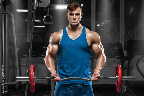 plakat Muscular man working out in gym doing exercises with barbell at biceps, strong male