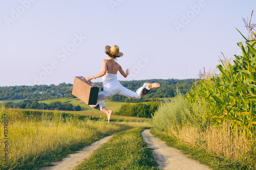 Joyful excited female jumping holding retro suitcase, sunny outdoors country road background. Backview
