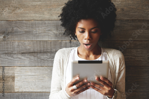 Portrait of beautiful shocked and astonished African woman with Afro hairstyle, holding tablet, reading surprising news on the Internet, opening mouth while posing against wooden wall background