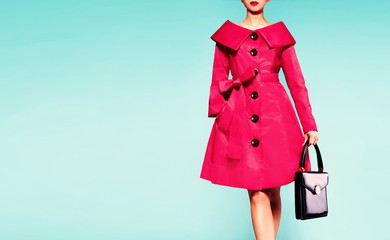 Colorful red trench coat woman with black leather handbag isolated on light blue background. Vintage retro mood fashion image.