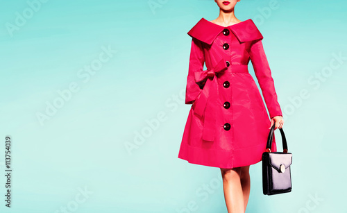 Fotografie, Tablou  Colorful red trench coat woman with black leather handbag isolated on light blue background