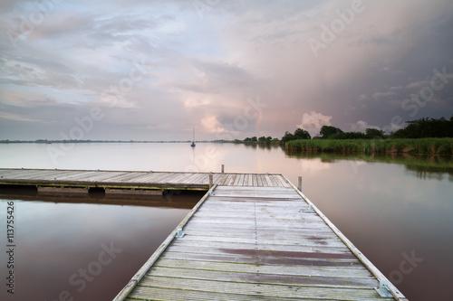 fototapeta na lodówkę wooden pier on lake during shower at sunset