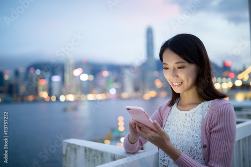 Woman watching on cellphone at night Poster