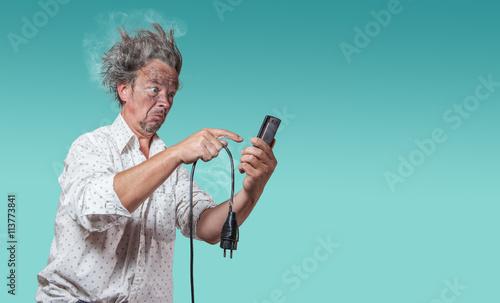 Fotografering mann mit verkohltem gesicht mit defektem kabel sucht auf smartphone nach hilfe
