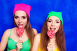 canvas print picture - Funny young women licking lollipops on blue background