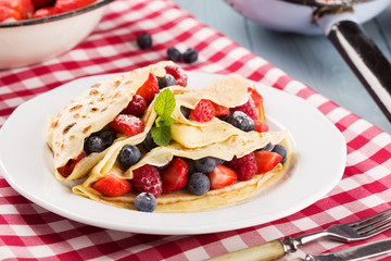Delicious pancakes with raspberries, blueberries and strawberrie