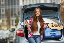 Brunette With Long Straight Hair And Brown Eyes,dressed In A Plaid Shirt And Blue Jeans,sitting In The Open Trunk Of The Gray Car Next To The Blue Suitcase,read SMS Message
