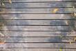 Top view of wooden walkway bridge with dry leaves