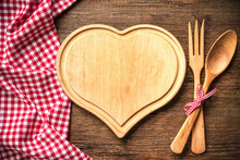 Heart Shaped Cutting Board With A Red Checkered Tablecloth