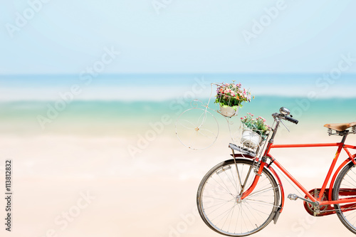 Papiers peints Velo Old red Bicycle with basket flowers on blured beach tropical sea