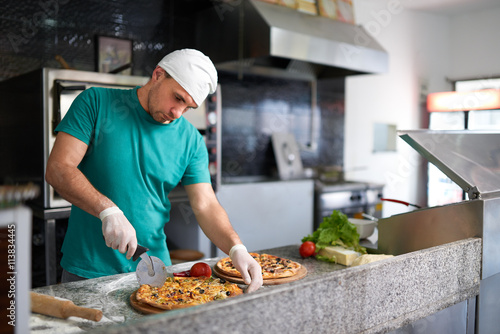 Poster Pizzeria Chef cuts freshly prepared pizza on a wooden substrate.