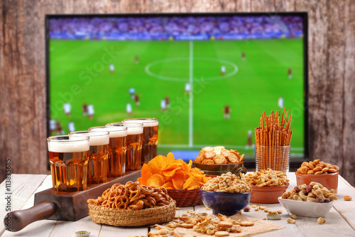 Papiers peints Biere, Cidre Beer and snacks set on football match tv background