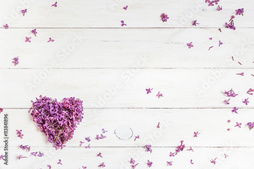 Spoed Foto op Canvas Lilac lilac flowers in the shape of heart on white wooden background, top view, flat lay