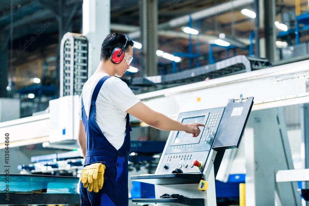Fototapeta Worker entering data in CNC machine at factory