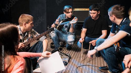 Obraz na PCV (fotoboard) Zespół muzyczny omawiający perkusistów w piosence. Widok z przodu na młodych muzyków siedzących na podłodze, wszyscy patrząc na faceta z podudzia.
