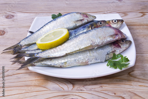 Photo  fish,  dish of sardines on wooden background