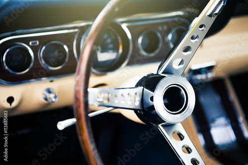 Photo  Inside view of classic american muscle car, with focus on steering wheel