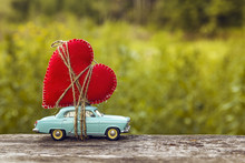 Miniature Blue Toy Car Carrying A Heart On The Blurry Natural Gr