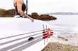 Woman with stand up paddle board at the coast