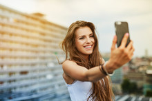Happy Young Woman Taking Selfi...