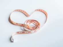 A Measuring Tape Shaping A Heart Isolated On Gray Background