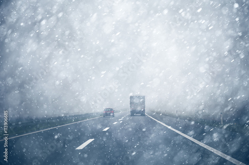 Fototapeta Car overtaking a truck on a heavy snowy, rainy and slippery highway. Dangerous overtaking at bad weather condition. obraz