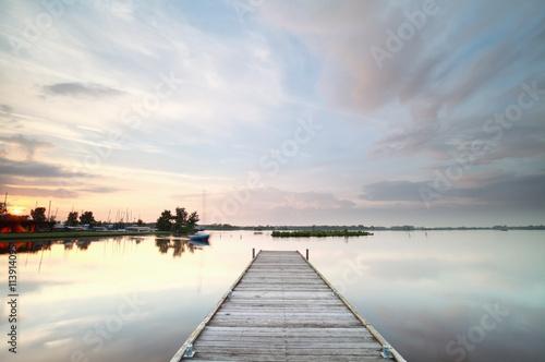 fototapeta na lodówkę wooden pier on big lake at sunset