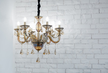 Panel Szklany Glass chandelier against a white wall from a brick