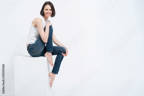 Fotografía  Beautiful young woman sitting on white cube in studio