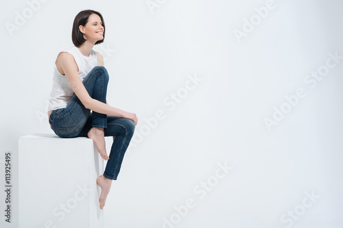 Fototapeta Beautiful young woman sitting on white cube in studio obraz