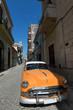 Orange american car parked in Old Havana under a blue sky
