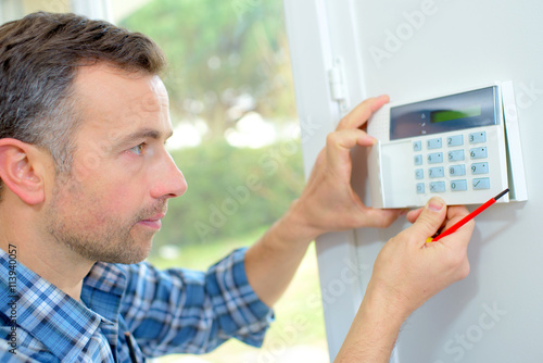 Electrician fitting an intrusion alarm Canvas Print
