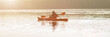 Man paddles canoe in river at sunrise