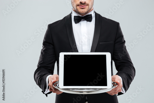 Fotografía  Blank screen tablet on tray holded by waiter in tuxedo