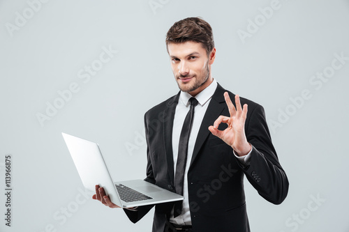 Fotografie, Obraz  Attractive young businessman holding laptop and showing ok sign
