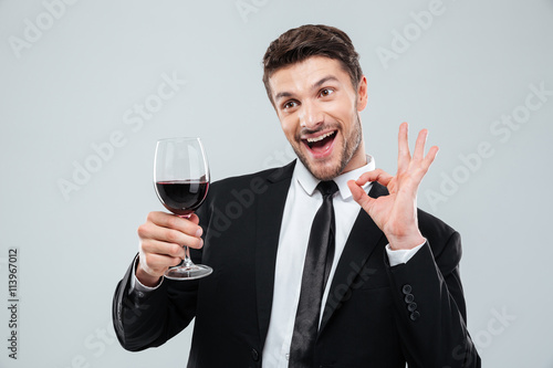 Fotografie, Obraz  Cheerful drunk businessman drinking red wine and showing ok sign