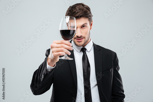 Focused young male sommelier looking at red wine in glass
