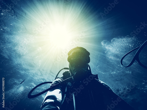 Spoed Foto op Canvas Duiken Man diving in the ocean with sun rays in the background.