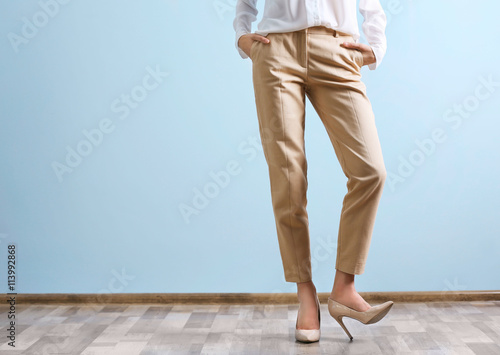 Beautiful young woman in a white shirt and beige pants on blue wall background