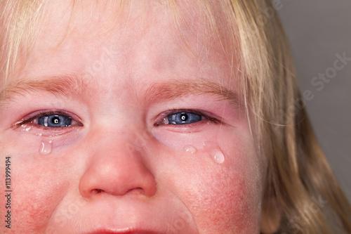 Foto Porträt von emotionalen Tränen schreiendes kleines blondes langes Haar des Babys
