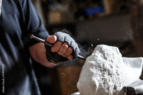 Carta da parati Close up of senior sculptor hands working on his marble sculpture in his worksho