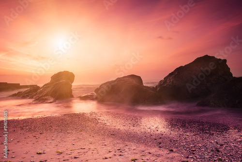 Spoed Foto op Canvas Koraal Summer seasonal natural vacation background. Romantic morning at sea. Big boulders sticking out from smooth wavy sea. Pink horizon with first hot sun rays. Long exposure.