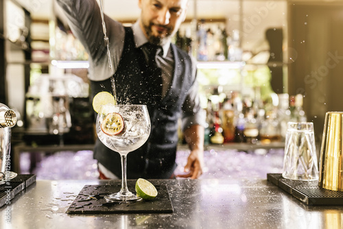 Barman is making cocktail at night club. Canvas