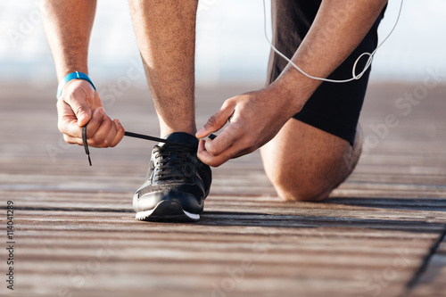 Sportsman laces his sneakers on pier Фотошпалери