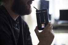 Close Up Of Man Using Vaporizer To Take Drugs At Home