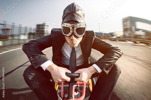 Fotografie, Obraz  Verrückter Geschäftsmann auf Tretauto