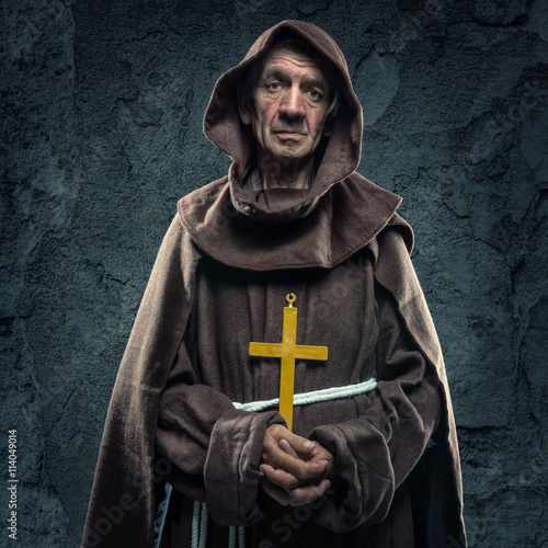 Fotomural Monk holding a wooden cross in front of the old walls