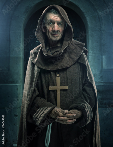 Photo Monk holding a wooden cross in front of the old walls