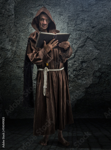 Cuadros en Lienzo Senior monk, priest holds in his hand the Bible